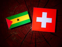 Sao Tome and Principe flag with Swiss flag on a tree stump isola. Ted Royalty Free Stock Photos