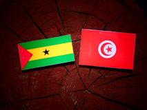 Sao Tome and Principe flag with Tunisian flag on a tree stump is. Sao Tome and Principe flag with Tunisian flag on a tree stump Stock Photography