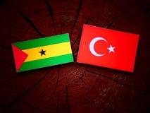 Sao Tome and Principe flag with Turkish flag on a tree stump. Sao Tome and Principe flag with Turkish flag on a tree stump Royalty Free Stock Image