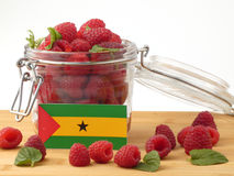 Sao Tome and Principe flag on a wooden panel with raspberries is Royalty Free Stock Image