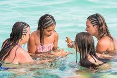 SAONA,多米尼加共和国- 2017年5月25日:人们在清楚的天蓝色的水中沐浴 复制文本的空间 库存照片