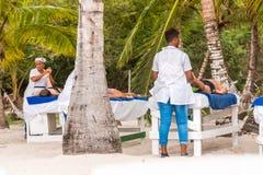 SAONA, DOMINICAANSE REPUBLIEK - 25 MEI, 2017: Masseurs op het zandige strand van het eiland Exemplaarruimte voor tekst royalty-vrije stock fotografie