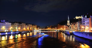 Saone River with boat sailing by night. And church Saint Georges on the right Royalty Free Stock Photo