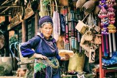 Sapa Lao Cai, Vietnam - 29 December, 2012: Ställningen för den gamla kvinnan på henne shoppar Arkivfoto