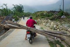 Sapa Vietnam - April 24, 2018: Den lokala mannen transporterar wood plankor på sparkcykeln arkivbilder