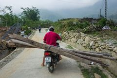 Sapa, Vietnam - 24. April 2018: Lokaler Mann transportiert hölzerne Planken auf Roller stockbilder
