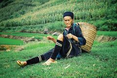 elderly black hmong tribe member woman resting home after a long day work at his farm spinning threads stock image
