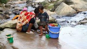 Sapa, Vietnam - 30 de noviembre de 2016: Una mujer del grupo étnico de Hmong negro lava la ropa en el río de la montaña adentro almacen de video