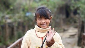 Sapa, Vietnam - 30 de noviembre de 2016: Una niña del grupo étnico de Hmong presenta al extranjero para la cámara almacen de metraje de vídeo