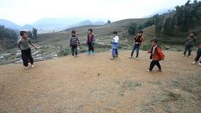Sapa Vietnam - December 01, 2016: Barn för etnisk minoritet som spelar en lek med snurrblast, i en landsbygd nära arkivfilmer