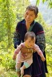 SAPA VIETNAM - MAJ 2014: den stam- Akha kvinnan bär behandla som ett barn byn Arkivbild