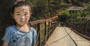 Small boy standing at the entrance of a hanging bridge leading to his house in Sapa, Vietnam royalty free stock images