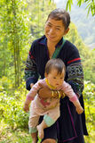 SAPA, VIETNAM - MAY 2014: tribal Akha woman carry baby village Stock Photography