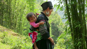SAPA, VIETNAM - MAY 2014: tribal native Akha woman carry baby stock video footage