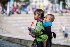 SAPA, VIETNAM - SEPTEMBER 03, 2017: Aziatisch jong meisje die haar broer op de straat in sapastad vervoeren stock foto's