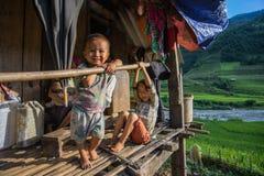 Sapa Vietnam -14 September 2014 - ett barn sitter framme av hans hus in Arkivfoton