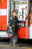 Sapador-bombeiro de sorriso Standing By Truck no fogo Foto de Stock
