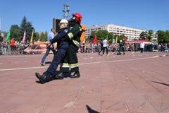 Sapador-bombeiro dos homens no terno à prova de fogo fora do perigo em exercícios, em competições da luta contra o incêndio, Mins foto de stock