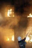 Sapador-bombeiro e homem ardente Imagens de Stock