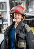 Sapador-bombeiro fêmea feliz Standing Against Imagens de Stock