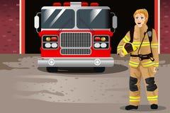 Sapador-bombeiro fêmea na frente do quartel dos bombeiros Imagem de Stock Royalty Free