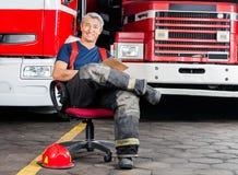 Sapador-bombeiro feliz Sitting On Chair contra caminhões Fotos de Stock Royalty Free
