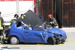 Sapador-bombeiro na ação para livre de um carro, ferida em um CRNA do carro Imagens de Stock
