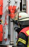 Sapador-bombeiro no carro de bombeiros com tubulação de água Foto de Stock