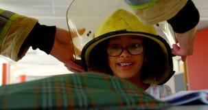 Sapador-bombeiro que ajuda a estudante afro-americano pondo o capacete sobre sua cabeça na sala de aula na escola vídeos de arquivo