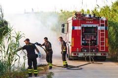 Sapador-bombeiro que extingue o fogo em Sicília fotografia de stock royalty free