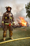 Sapador-bombeiro real com a casa no fogo no fundo Foto de Stock Royalty Free