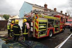 Sapadores-bombeiros e motor no incêndio da casa Fotografia de Stock Royalty Free
