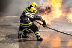 Sapadores-bombeiros na ação Treinamento do departamento dos bombeiros Imagem de Stock