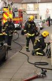 Sapadores-bombeiros no incêndio da casa Imagens de Stock