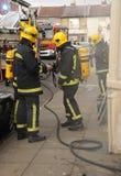 Sapadores-bombeiros no incêndio da casa Fotografia de Stock