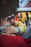 Sapadores-bombeiros que ajudam uma mulher ferida em um carro Fotografia de Stock Royalty Free