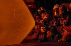 Sapadores-bombeiros que atacam um fogo Imagem de Stock