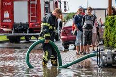 Sapadores-bombeiros que bombeiam para fora a água Imagem de Stock Royalty Free