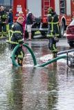 Sapadores-bombeiros que bombeiam para fora a água Fotografia de Stock