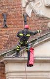 Sapadores-bombeiros que escalam com cordas e equipamento de escalada em um ol fotografia de stock