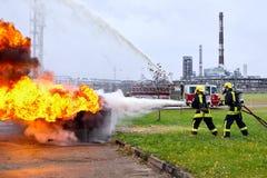 Sapadores-bombeiros que extinguem o fogo na perspectiva do re Imagens de Stock