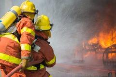 2 sapadores-bombeiros que pulverizam a água na operação da luta contra o incêndio Fotos de Stock