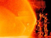 Sapadores-bombeiros que trabalham em um fogo Imagem de Stock
