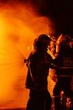 Sapadores-bombeiros que trabalham um fogo Fotos de Stock Royalty Free