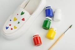 Sapata branca com corações pintados coloridos fotografia de stock royalty free