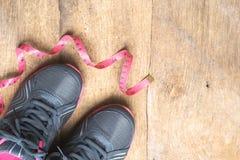Sapata da sapatilha dos esportes com a fita de medição no fundo de madeira Imagens de Stock Royalty Free