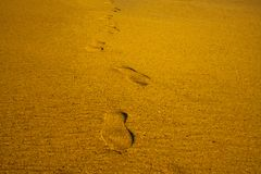 A sapata dos passos imprime marcas no verão das férias do mar da praia da areia imagem de stock royalty free