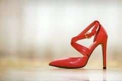 Sapata fêmea do entalhe vermelho de couro elegante do salto alto com as curvaturas douradas isoladas no fundo claro do espaço da  imagem de stock