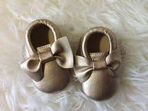 Sapata pequena do ouro do bebê no fundo macio branco fotos de stock royalty free