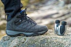 Sapata Trekking e close up binocular em uma rocha nas montanhas durante um dia ensolarado, fundo borrado imagem de stock